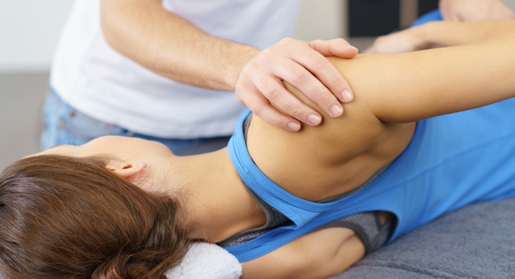 Male Osteopath Stretching the Injured Body of his Female Patient Lying on a Therapy Bed.